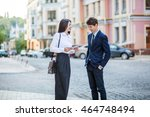 Small photo of Business acquaintance of handsome businessman in blue suit and beautiful businesswoman in white blouse and black skirt. First meeting. Communication on city background.
