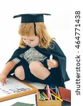 Small photo of Little boy child in black academic gown and squared hat playing with drawing school board holding marker near box with colored pencils isolated on white background