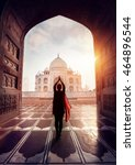 Small photo of Woman doing yoga tadasana tree pose with flying red scarf in silhouette near Taj Mahal in Agra, Uttar Pradesh, India