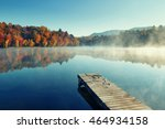 Stock photo autumn foliage and fog lake in morning with boat dock 464934158