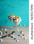Small photo of Two servings of ambrosia fruit salad in martini glasses. Against turquoise background with scattered marshmallows, pecans, and blueberries.