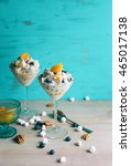 Small photo of Two martini glasses filled with ambrosia fruit salad against turquoise background.