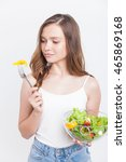 Small photo of Girl with bowl of salad looking with doubt at piece of bell pepper. Concept of diet slip off.Organic fitness