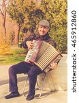 Small photo of Musical passion at the street - Vienna, Austria - March 31, 2016: Passionate accordionist playing at a park in Vienna city, Austria, Europe.
