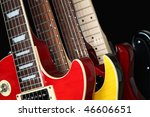Closeup of four electric guitars isolated over a black background. - stock photo