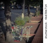 Small photo of An overturned shopping cart trolley with possessions of a homeless person on a brick walkway sidewalk of Houston Downtown. Concept for failure of society adequate systems, funding and support. Vintage