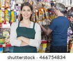 Saleswoman Standing Arms Crossed While Customer Selecting Produc