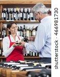 Saleswoman Giving Wine Bottle...