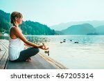 Stock photo beautiful woman in lotus position meditating by the lake sunset water birds 467205314