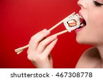 a girl eating a sushi roll. | Shutterstock . vector #467308778
