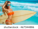 Surfer girl walking with board on the sandy beach. Surfer girl. Beautiful young woman at the beach. water sports. Healthy Active Lifestyle. Surfing. Summer Vacation. Extreme Sport.