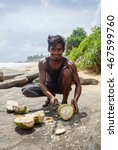 Small photo of Young man chopping a coconut on the beach. Sri Lanka, Ambalangoda. 29 May 2016