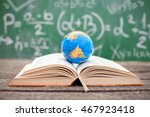 globe standing on open book  | Shutterstock . vector #467923418