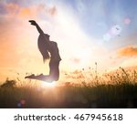 Stock photo vitality concept silhouette of a woman jumping with her hands raised at sunset meadow background 467945618