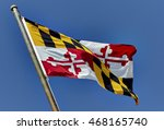 Maryland state flag blowing in the wind on flag pole against blue sky