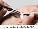 Small photo of beautician holding tweezers with a cilium, eyelash
