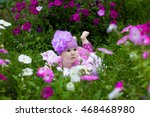 Small photo of A little girl lies in Park and gets acquainted with the purple flowers on the green grass. The concept of childhood and the happiness of children. Novorozhdennyh babe on a beautiful floral background.