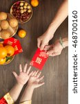 Small photo of Chinese lunar new year flat lay traditional food and offering on table top. Senior women hands giving red packet to toddler boy hands.