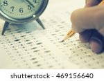 Small photo of alarm clock, optical form of standardized test with answers bubbled and a black pencil examination,Answer sheet,education concept,selective focus,vintage