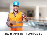 Smiling manual worker in blue helmet with digital tablet and gesture thumb up - stock photo