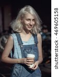Small photo of Portrait of beautiful Caucasian teenage young blonde alternative model girl woman in blue tshirt, jeans romper looking in camera holding cup of coffee, toned with Instagram filters