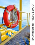 Small photo of Life buoy or Ring buoy and rope is safety equipment for rescue worker or man over board in petroleum offshore wellhead remote platform, Energy and petroleum industry is major of the world.