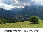 A solitary tree on grassy hilltop under sunshine & the beautiful La Villa village in the green valley with majestic mountains in background under moody sky in Dolomites, Trentino, South Tyrol, Italy - stock photo