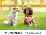 Stock photo cute african american girl playing with dog in park 469861076