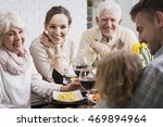 Small photo of Mother and grandparents stare adoringly at his grandson during dinner