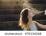 young woman spraying face with...   Shutterstock . vector #470134268
