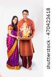 Small photo of portrait of smart Indian couple holding Ganesh idol or ganpati idol over white background