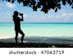 lady shooting video at beach   Shutterstock . vector #47063719