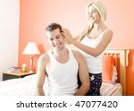 Woman ruffles man's hair as they relax in their bedroom. Horizontal format. - stock photo