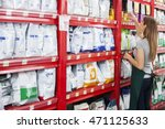 Stock photo saleswoman arranging food packages in pet store 471125633