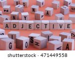Small photo of ADJECTIVE word on wooden cube isolated on orange background