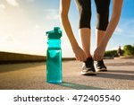 woman tying her shoe next to... | Shutterstock . vector #472405540