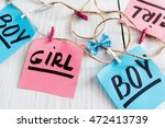 Small photo of Handmade greeting garland for newborn kids. Pretty chaplet made with pink and blue stickers and twine on white background. It's a girl and boy twins concept