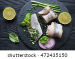 Stock photo herring fillet rolls on a stone slate tray above view close up 472435150