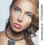 Small photo of Portrait of charming girl with blue eyes and a necklace abound his neck