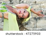 Beautiful belly dancer in green on the ancient stairs of Kourion amphitheatre in Cyprus. - stock photo