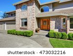 Luxury Brick house with porch view and trimmed shrubs.  Northwest, USA