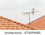 tv antenna on red roof | Shutterstock . vector #473099680