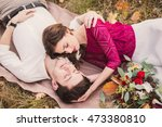 Small photo of Stylish and romantic caucasian couple lie on the grass and leaves in the beautiful autumn park. Love, relationships, romance, happiness concept.