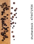 Small photo of Spices allspice and black pepper on wooden plate isolated top view. With place for text.