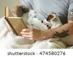 Stock photo man with cute dog reading book 474580276