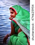 Small photo of MATHURA, INDIA - March 23, 2016 : Unidentified Indian woman with green saree sitting on the banks of river Yamuna. Mathura is a city in the North Indian state of Uttar Pradesh.