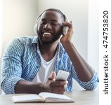 Small photo of Handsome Afro American businessman in casual clothes and headphones is listening to music using a smart phone and smiling while sitting at home