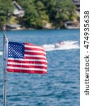 Small photo of American Dream - US flag, boat, and cottage