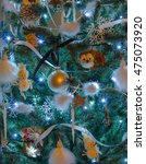 Small photo of Various decorations in christmas tree with blue lights and yellow ambient light