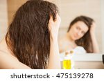 young woman applying oil mask... | Shutterstock . vector #475139278